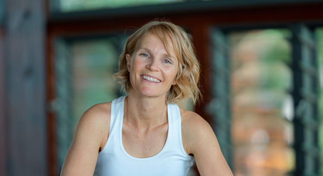 Image of Gwinganna's Retreat Manager, Katlyn, sitting and smiling wearing white tank top.