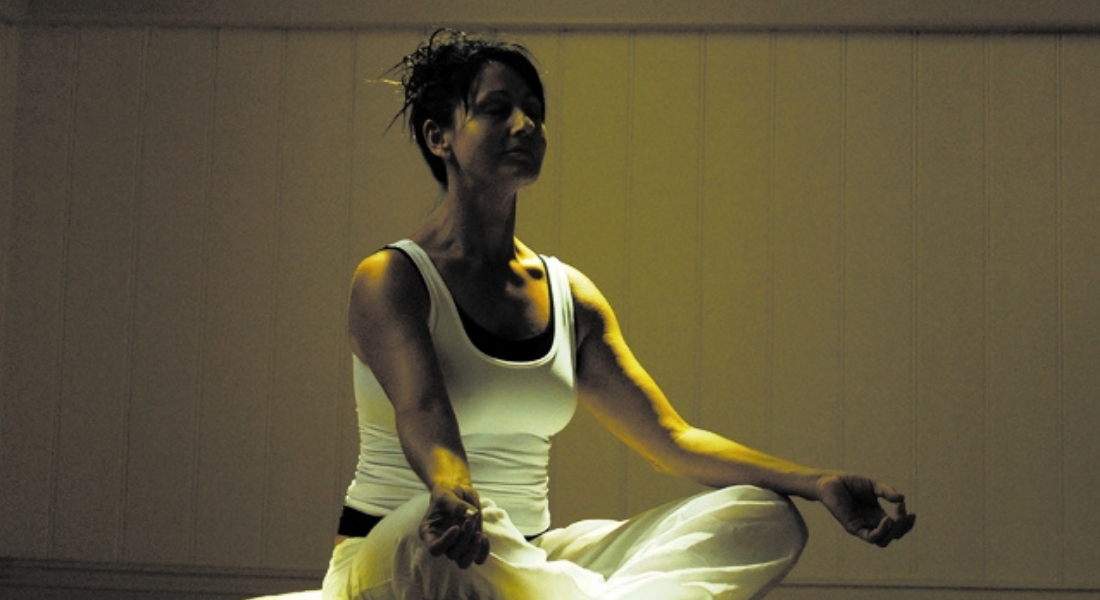 Woman in white tank top and white pants sits in meditation position