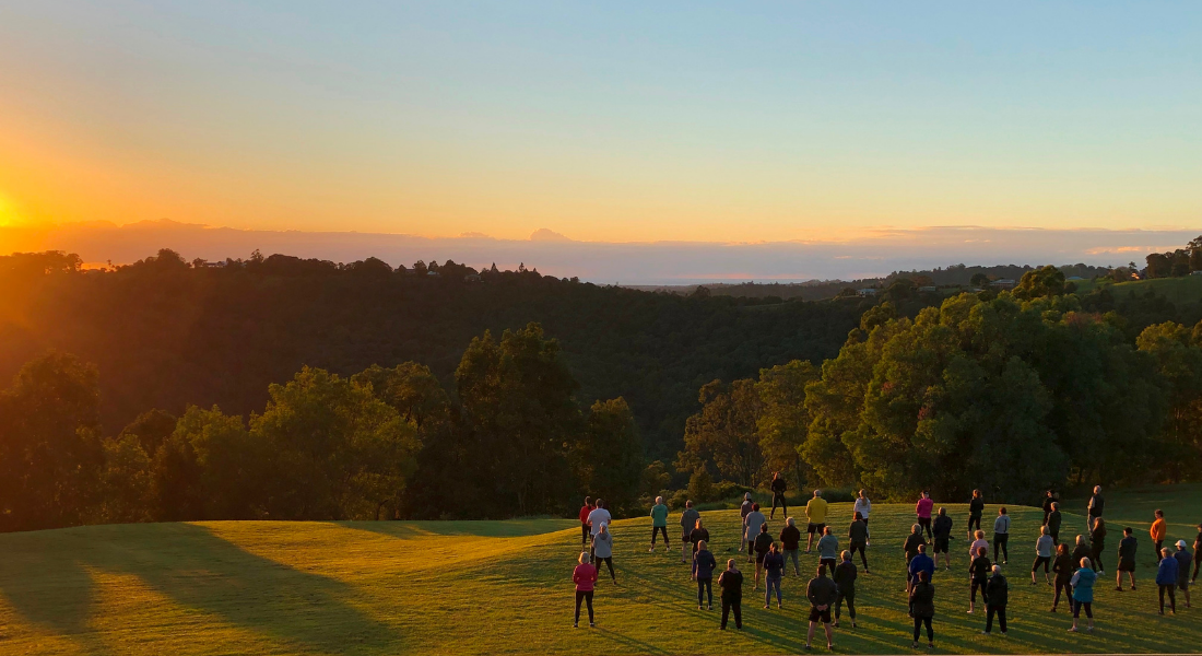 Group of Gwinganna guests practising Qi Gong as sun rises