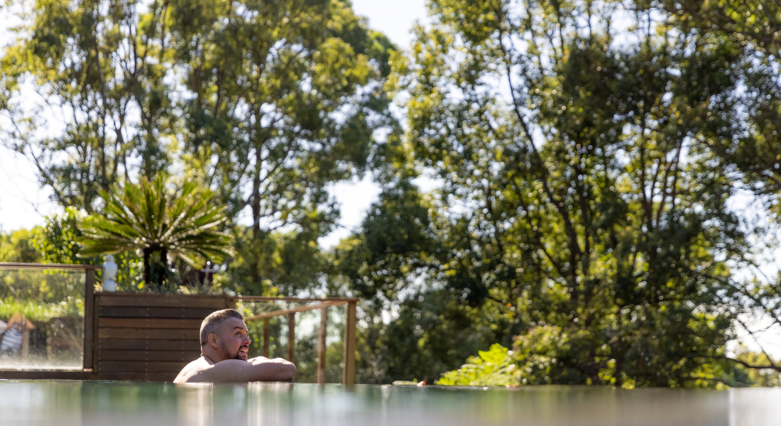 man swimming in Gwinganna pool overlooking trees